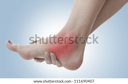 Pain in a woman ankle. Female holding hand to spot of ankle-ache. Concept photo with Color Enhanced skin with read spot indicating location of the pain.
