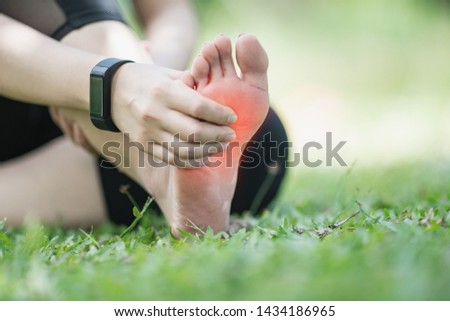 pain in foot, girl holds her hands to her feet, foot massage, cramp, muscular spasm, red accent on foot Stok fotoğraf ©