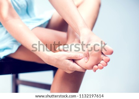 Pain in the foot, girl holds her hands to her feet, foot massage, cramp, muscular spasm, red accent on the foot, close-up Stok fotoğraf ©