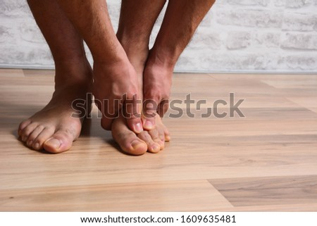 Pain in the foot, man holds hands to his feet, foot massage, cramp, muscular spasm, red accent on the foot, close-up Stok fotoğraf ©