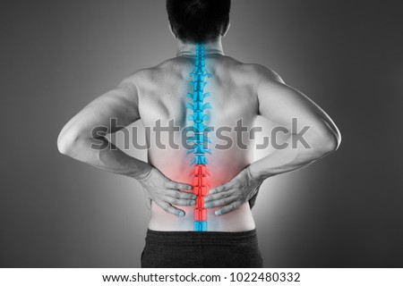 Pain in the spine, a man with backache, injury in the lower back, black and white photo with highlighted skeleton