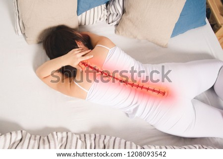 Pain in the spine, woman with backache at home, back injury, photo with highlighted skeleton