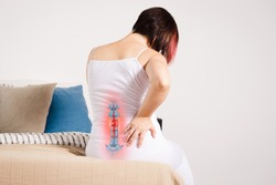 Pain in the spine, woman with backache at home, injury in the lower back, photo with highlighted skeleton