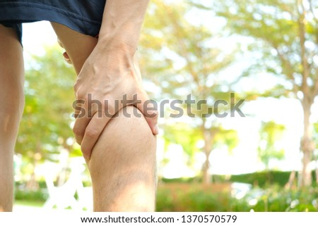 Pain Leg of man standing on grass in the park her  massage calf muscles  and stretch the muscles
