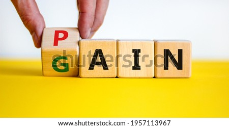 Pain or gain symbol. Businessman turns the wooden cube and changes the word pain to gain. Mindset for career growth business. Beautiful white background. Business, pain or gain concept. Copy space. Stock photo ©