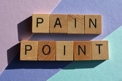 Pain Point, buzzword phrase in wooden alphabet letters isolated on colour background