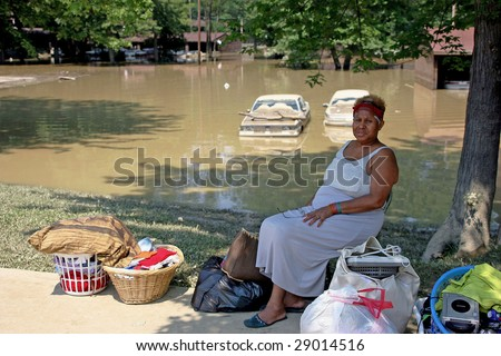 PAINESVILLE, OHIO - JULY 16: An unitentified woman sits with her only remaining items saved from her home.  July 16th 2006 in Painesville, Ohio.