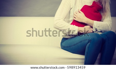Painful periods and menstrual cramp problems concept. Woman having stomach cramps sitting on cofa feeling very unwell holding hot water bottle to feel some relief #598913459