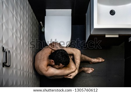 Painful picture of young man sitting on floor in rest room and suffer. He is naked and lonely. Guy has problems. He cry and feel exhaustion.