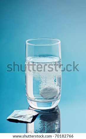 Painkiller tablet in glass of water with bubbles over blue background. Vertical. copy-space.