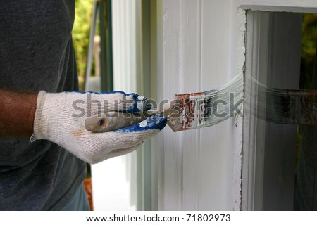 Painstakingly painting around windows of a house