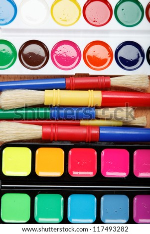 Paint and brushes on a wooden table.