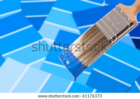 Paint brush loaded with blue paint with colour swatches below
