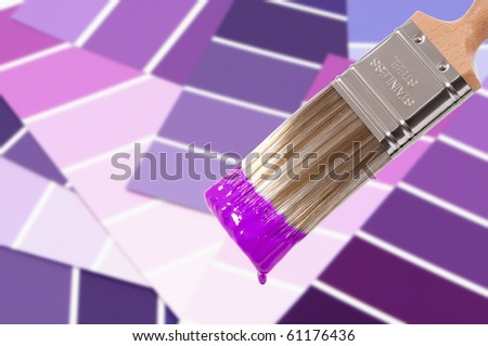 Paint brush loaded with purple paint with colour swatches below