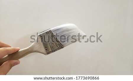 Paint brush on the table. White dirty brush on wall background. Free space for text. Design paint brush tool.