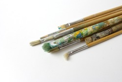 paint brush on white background. A bunch of brushes for oil painting. Paint brushes stained with paint. Multi-colored drawing tools. Professional brushes for painting on canvas.