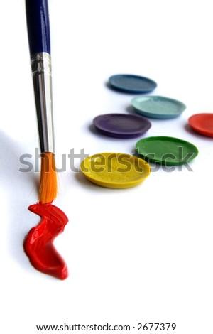 Paint brush, red paint,  and paint pallet closeup