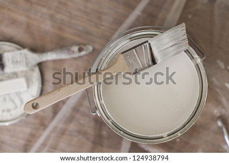 Paint brush resting on paint tin viewed from above