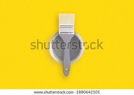 Paint brush with an open can of paint on trendy yellow background. Colors of the year 2021 - Illuminating and Ultimate Grey.
