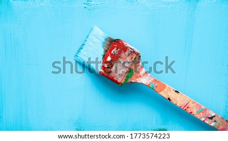 Paint brush with blue paint on a freshly blue painted background
