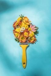 Paint brush with flower on abstract lake.  Flat lay. Copy space. Minimal creative concept.