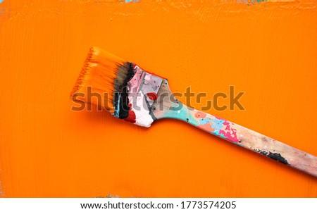 Paint brush with orange paint on a freshly orange painted background
