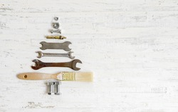 Paint brush wrench, nuts and bolts decorated as Christmas tree on a white wooden background. Christmas greeting card and Happy new year greeting card concept. Top view with copy space for your text