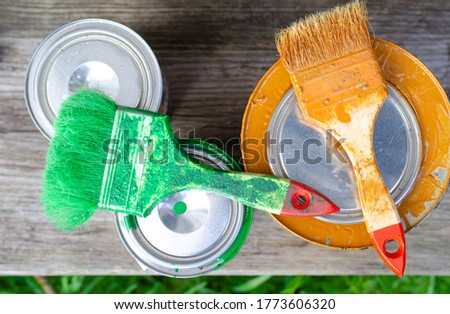Paint brushes and acrylic paint cans with green and brown paint on a wooden bench. flat lay background with copy space. Concept of do it yourself DIY, home renovation.