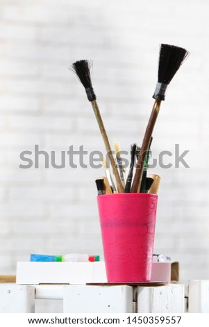 Paint brushes are in the cup. Photo on the background of a white wall with a brickwork effect. Concept hobbies and hobbies.