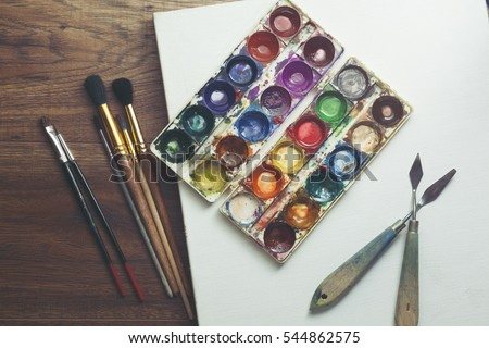 paint brushes in blank canvas on wooden background