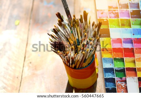 Paint brushes in the cup and palette water paints are on the table #560447665
