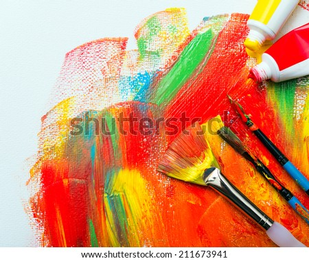 Paint brushes on a painted canvas