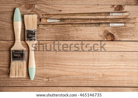 paint brushes on a wooden background #465146735
