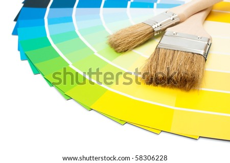 Paint brushes with colour swatch cards on white background