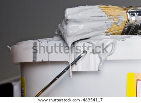 Paint bucket and paintbrush over gray wall