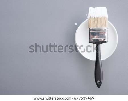 Paint bucket with paint brush on grey  background,top view