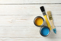 Paint cans and brushes on wooden background, top view