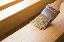 Paint coating and protection of wooden surfaces.Brush that covers wooden planks and beams with varnish for interior work in the color of oak.