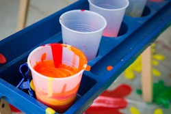 Paint mixed in plastic cups on an easel tray