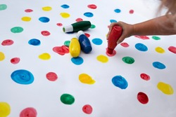 Paint of child in multicolor dots. Creative and sensory play of children. Color of childhood and little hand of kid. Stay at home. Close up.