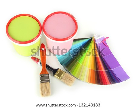 Paint pots, paintbrushes and coloured swatches isolated on white