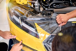 Paint protection film installation on fender panel surface of luxury sports car. PPF is polyurethane film applied to car surface to protect the paint from rock chip and scratch. Shallow DOF. Hand move