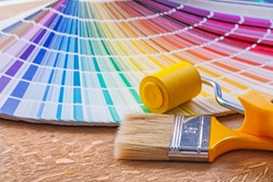 Paint roller brush and pantone color palette guide on wooden board close up view