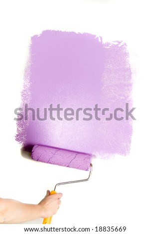 Paint roller in hand. Painting the wall.