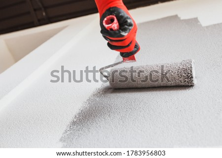 Photo of  Paint roller on the wall during painting - renovation of the building facade in dark gray