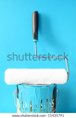 paint roller on top of blue paint can for home decorating