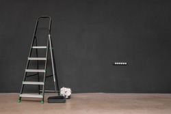 Paint roller, step ladder on the black wall background with copy space.