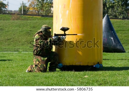 Paintball player aiming and shooting with marker