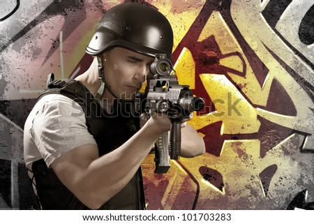Paintball player on graffiti background with intense orange light