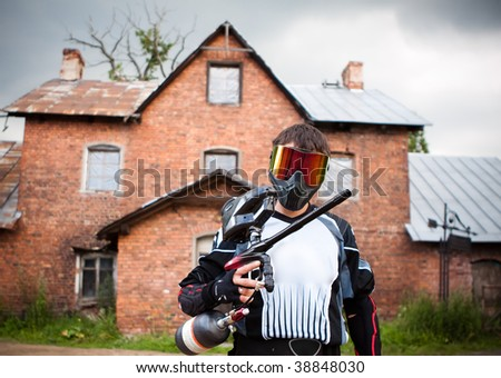 paintball shooter and house as the background